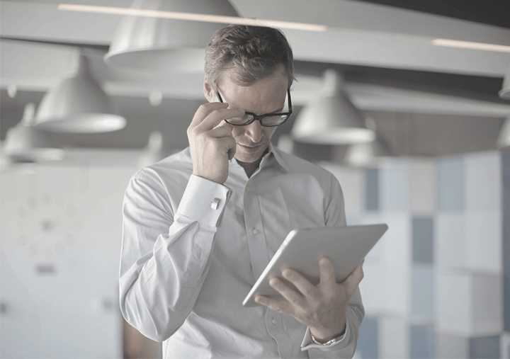 Man standing in the offices of our Marketing Agency in Warwickshire, reading information on a tablet, whilst holding his glasses to concentrate