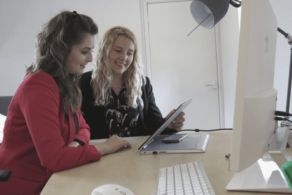 Two ladies sitting at a desk looking at a tablet device within a marketing agency in Warwickshire