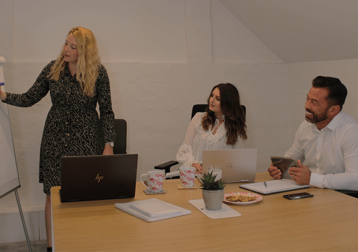 One woman presenting to two team members about a strategy for their marketing agency in Warwickshire